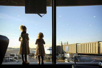 Rear view of sisters looking through window while standing at airport