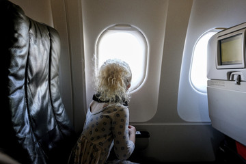 Side view of girl looking through airplane window