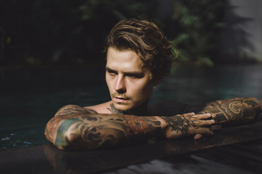 Close up of thoughtful tattooed man in swimming pool