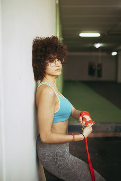 Side view of thoughtful woman wrapping her hand with boxing bandage against wall in gym