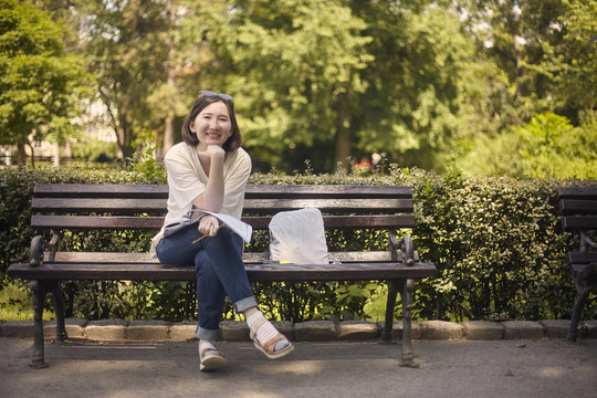 Full length portrait of smiling young woman sitting on bench at park