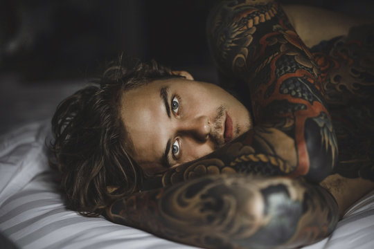 Close up portrait of shirtless tattooed man lying on bed at home