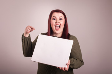 Woman holding a blank board pointing a finger at blank sign excited happy facial expression