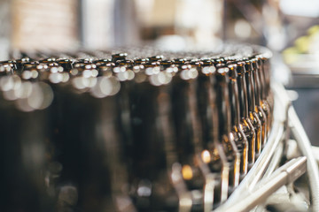 Close-up of beer bottles on machinery at brewery