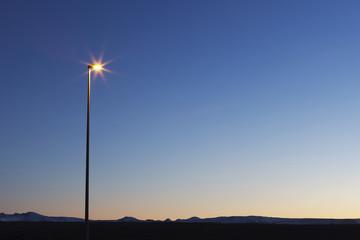 Illuminated street light against clear blue sky at night