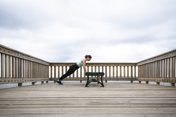 Woman doing push-ups on bench at pier against cloudy sky