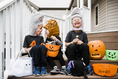 Playful siblings in Halloween costumes sitting on steps against house