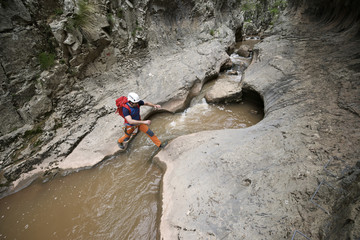 High angle view of backpacker crossing stream on rocks in forest