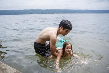 Shirtless father teaching daughter wearing mermaid costume to swim in lake