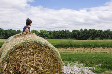 Boy sitting on hay bale against cloudy sky at farm