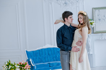 guy with girl in white room. Loving couple on background of sofa. girl in white dress.