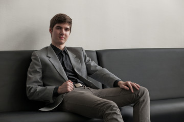 Handsome young man in suit sitting on couch in reception. Business man waiting for meeting.
