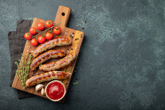 Fried sausages with sauces and herbs on a wooden serving Board. Great beer snack on a dark background. Top view with copy space