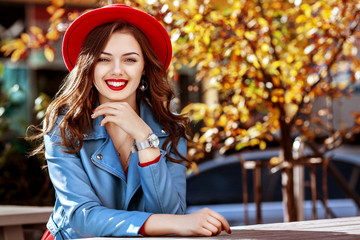 Wall Mural - Outdoor portrait of young beautiful happy smiling girl with long hair, red lips, wearing stylish hat, blue jacket posing in autumn street. Lifestyle, autumn fashion concept. Copy, empty space for text