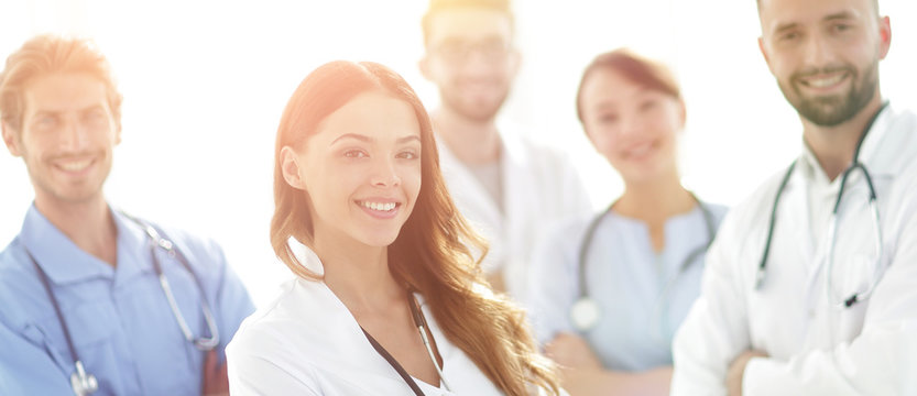 Attractive female doctor with medical stethoscope in front of medical group