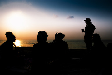 Silhouette of group of friends hanging out on the beach.