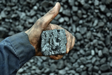 Hand of the miner shows coal and OK in the mine