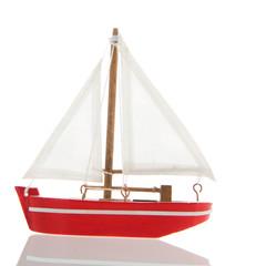 Miniature red sail boat