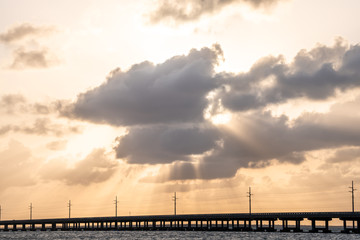 Overseas highway bridge road at Bahia Honda key state park during dramatic sunset with sun behind clouds, god rays, power electricity lines, water, waves