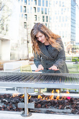 Portrait of young woman standing on street above rectangular fire pit burner, heating table furniture on patio, outside, outdoors, warming hands from flame on cold day