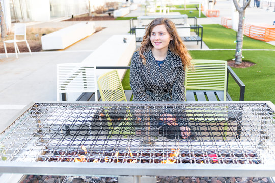 Young, smiling woman sitting on street by rectangular fire pit burner, heating table furniture on patio, outside, outdoors, warming hands from flame on cold day