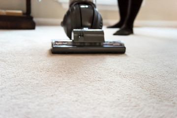 Closeup of woman, female doing cleaning at home with vacuum cleaner showing head, brush on carpet floor