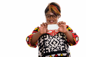 Studio shot of happy fat black African woman smiling while takin