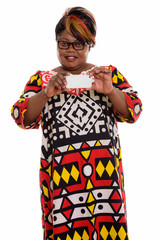 Studio shot of happy fat black African woman smiling and standin