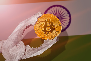 BITCOIN (BTC) coin being squeezed in vice on India flag background; concept of cryptocurrency bitcoin under pressure. Prohibition of cryptocurrencies, regulations, restrictions or security