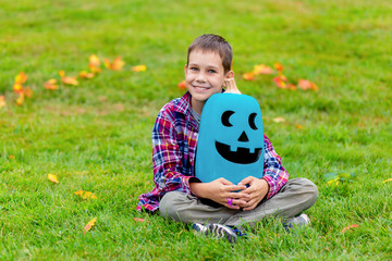 happy boy excited by Halloween. the child holding a teal pumpkin as a symbol of the safe trick-or-treating. Copy space for your text