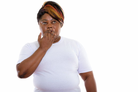 Studio shot of fat black African woman thinking while covering m