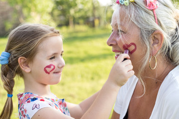 Cute girl making up her grandmother