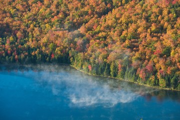 Morning mist on Heart lake surrounded by fall foliage
