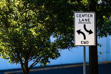 Center lane ends sign with trees, road, and a warehouse
