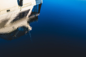 Abstract boat reflection on a deep blue dark harbor