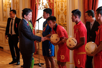 Japan's Prime Minister Shinzo Abe shakes hands with U-17 soccer team players during a photo session at the 10th Mekong-Japan Summit meeting in Tokyo