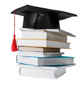 stack of different colored books with a graduation cap