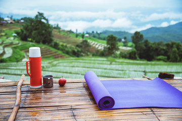 Purple yoga mat and red water bottle with a glass of water stainless Put forward. And Red apple on wooden background. On the balcony landscape Natural Field.Travel relax. papongpieng in Thailand