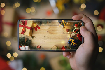 Hand Taking Picture of Christmas Decoration With Infinite Display Smartphone