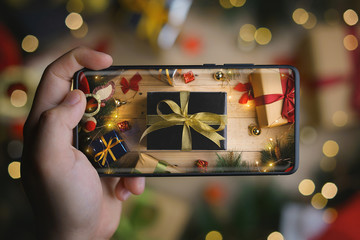 Hand Taking Picture of Black Gold Christmas Present With Infinite Display Smartphone