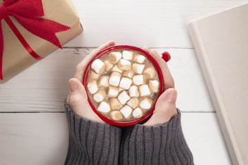 Person Holding a Hot Chocolate with Marshmallows on a Wooden Table with a Gift and a Novel to Read