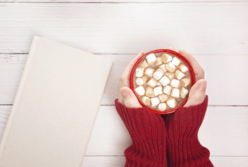 Personal Holding a Mug of Hot Chocolate with Marshmallows with a Novel to Read