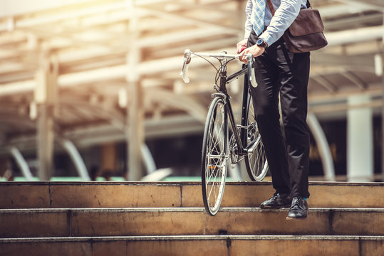 Smart Businessman Holding Bicycle goto Work on Urban Sidewalk in Rush Hour  - Eco Friendly and Lifestyles Concept
