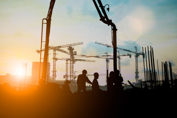 Silhouette of engineer and construction team working at site over blurred background for industry background with Light fair.Create from multiple reference images together.