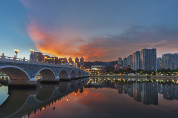 Residential building and bridge in Hong Kong city under sunset