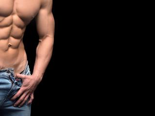 Closeup torso of shirtless muscular man posing on a black background