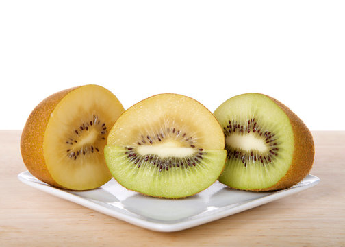 Kiwi and sungold kiwi sliced in half two types merged on white plate on wood table. Kiwifruit, or Chinese gooseberry is the edible berry of several species of woody vines in the genus Actinidia