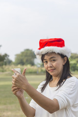 Woman in santa hat taking picture by smatrphone