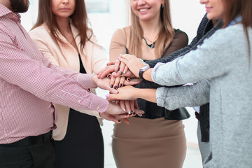 portrait of confident business team stacking hands