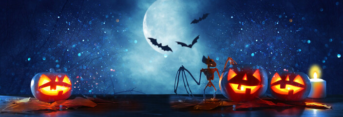 Halloween holiday concept banner. Pumpkins over wooden table at night scary, haunted and misty forest.